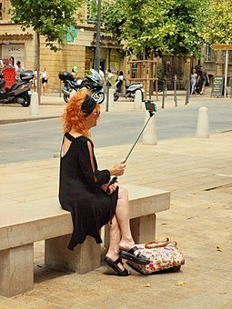 Woman taking a selfie using a selfie stick