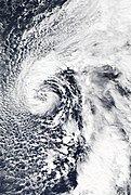 A non-tropical cyclone with clouds wrapping cyclonically around an open center; a distinct front can be seen to the southeast of the storm