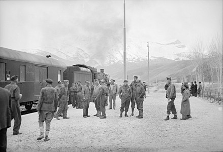 American and British Army train crewmen standing at a station. An American locomotive is seen at the head of the train at left. c. 1943 American and British soldier trainmen standing about at a station on the route for supplies to Russia. An American engine is seen at the head of the train at left, somewhere in Iran.jpeg