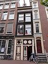 foto van Huis met gevel onder rechte klossenlijst waarop een rondbogige dakkapel