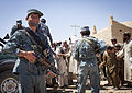 An Afghan National Civil Order Police (ANCOP) officer provides security as fellow officers hand out radios and comic books to residents in Delaram, Helmand province, Afghanistan, May 26, 2013 130526-M-RO295-157.jpg