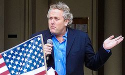 Photograph of Andrew Breitbart shrugging while speaking at an event