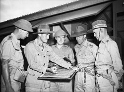 A group of military officers in conference around a map