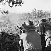 Soldiers firing a machine-gun towards a hillside in the distance. A large number of discarded ammunition belts are visible.