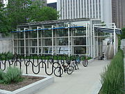 Rows of outdoor bike racks in a plaza in front of a building
