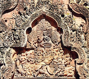 Ravananugraha - An elaborate portrayal of the Ravananugraha scene at Banteay Srei. A multi-tiered Kailash depicts many sages, divinities on it, while animals run terrified in the bottom tier. On the top of the Mount, a Shiva calm sits with a scared Parvati on his lap.