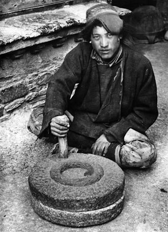 Tibetan wearing the typical hat operating a quern to grind fried barley. The perpendicular handle of such rotary handmills works as a crank (1938 photo). Bundesarchiv Bild 135-BB-152-11, Tibetexpedition, Tibeter mit Handmuhle.jpg