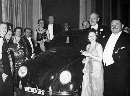 German Press Ball, January 1939.Dr. Ferdinand Porsche, fourth from the left, presents the Volkswagen tombola prize to Mrs. Elsa Ellinghausen, the lucky winner.
