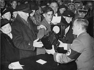 Eumig - Distribution of 500 small receivers (DKE38) manufactured by EUMIG, on the occasion of Joseph Goebbels' 41st birthday in the Berlin Radio House in October 1938. The Nazi official with swastika armband distributing them is Werner Wächter, the District Manager for Propaganda.