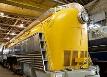 A yellow, streamlined steam locomotive.