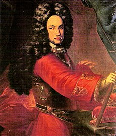Man with long, dark curls and red tunic