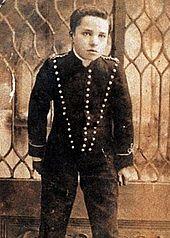 Photo noire et blanc d'un enfant en costume devant une grande fenêtre.