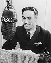 "A man in dark, formal military uniform leaning forward towards a microphone labelled ""BBC""."