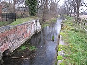 View downstream of the lock chamber build for the Sleaford Navigation, to maintain the head at the mill.  The chamber is largely brick built with stone details for load-bearing parts, and the brick is coloured with moss and lichen.  A little desultory grass covers the top sides.  There are no lower gates, the lock having been converted into a weir many years ago.  A cheap iron railing fence, painted black recently, delineates the property associated with the mill and restaurant to the left. This is a winter view and many bare trees line the banks downstream. The trunks of the nearest can be clearly seen to be covered in ivy.  The water looks clear and placid.