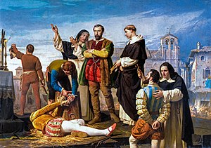 Two men and a priest stand in the center, overseeing the proceedings. A dead body lies on the ground; a man triumphantly lifts up his severed head in the background. A bearded man with hands bound is being brought forward to be executed next.