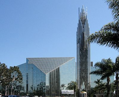The Crystal Cathedral is a built in a modern style with panels of glass set in metal frames making both the walls and roof. A tall tower of the same materials rises beside it