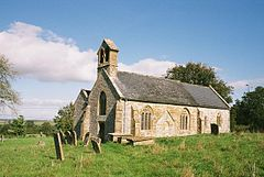 Stone building with arched windows. In the foreground are gravestones.