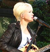 Cyndi Lauper playing a guitar.