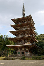 Five-storied wooden pagoda with white walls and vermillion red beams.