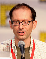 A closeup of a man in front of a microphone. He has a receding hairline and wears dark-framed glasses.
