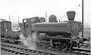 A pannier tank locomotive with a conical chimney is pulling a shunter's wagon and guards van.