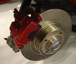 Brake lining - In this view of an automobile disc brake, the brake pad is the black material held by the red brake caliper.  The brake lining is that part of the brake pad which actually contacts the metal brake disc (rotor) when the brake is engaged.