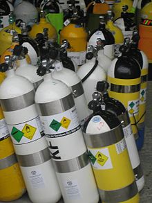 A large number of scuba cylinders and twin sets of different colours stacked together