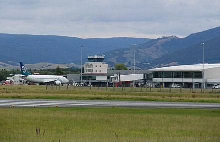 Dunedin International Airport control tower and terminal building in 2009 with an Air New Zealand Boeing 737-300 on the tarmac Dunedin International Airport2.jpg