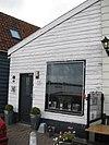 foto van Houten huis met houtskelet, de voorste helft in de 19e eeuw met een verdieping verhoogd. Uitwendig aspect, met puntvormig voorschot, 19e-eeuws