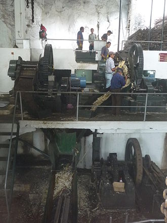 Bagasse - Sugarcane being crushed in Engenho da Calheta, Madeira. The bagasse falls down a chute and is removed on a conveyor belt below