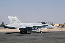 Photo of a modern fighter aircraft moving along tarmac. Sand and buildings are visible in the background.