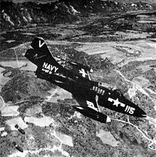 A single seat jet aircraft with US Navy markings in mid-air, flying in profile from left to right in a downward angle of attack below the camera. To the bottom left, two bombs are falling away from the aircraft towards an unseen target in the fields below.