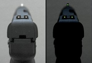 Photo of the tritium-illuminated fixed sights of the Five-seven USG pistol, in normal and dim lighting.