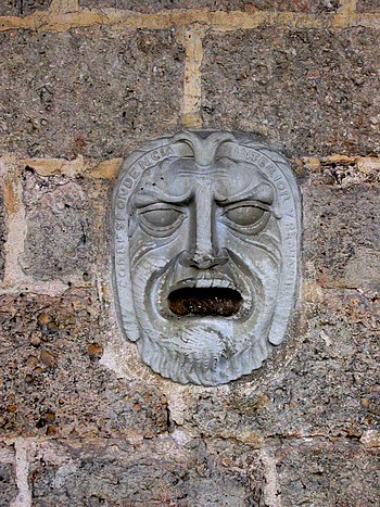 Face sculpture embedded in wall in Cuba