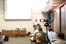 image of a camera on a tripod with microphone at the back of a presentation room