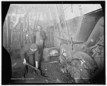 Two dirty men feeding coal into an oven in a rather gloomy looking room
