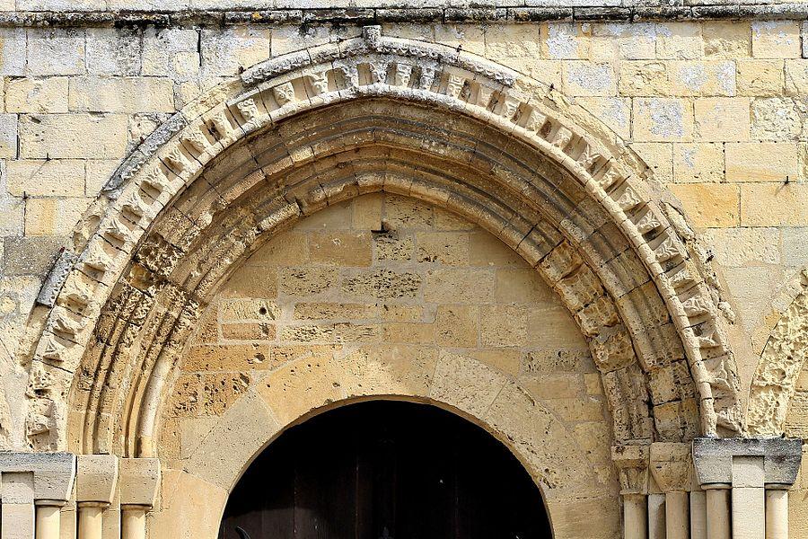 Archivolte garnie de têtes plates à barbe du portail principal de l'église Saint-Pierre de Fontaine-Étoupefour (Calvados)