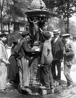 Wallace fountain - People drinking from a Wallace fountain during Bastille Day celebrations in 1911