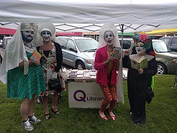 Four individuals in costume showing off books at ECM Pride 2018.jpg