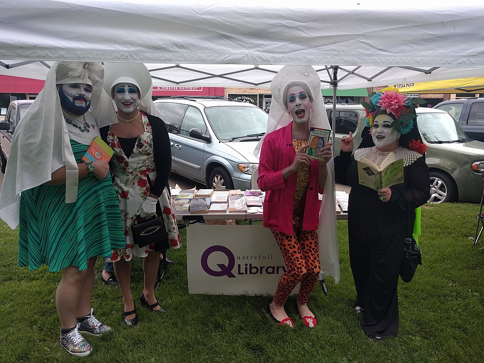 Four individuals in costume showing off books at ECM Pride 2018
