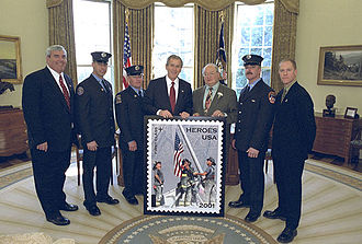 Raising the Flag at Ground Zero - White House photo of March 11, 2002, unveiling of Heroes stamp.  From left Postmaster General John E. Potter; Firefighters Billy Eisengrein and George Johnson; George W. Bush; U.S. Rep. Gary Ackerman, 5th District, N.Y. (who sponsored the stamp); Firefighter Dan McWilliams; and Record photographer Thomas E. Franklin, who took the photo featured on the stamp