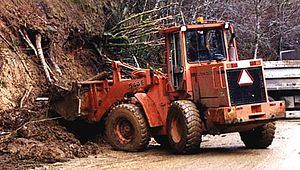 Heavy equipment operator - A wheeled front loader at work. This wheeled tractor is equipped with a large bucket, which can be raised or lowered by hydraulic arms.