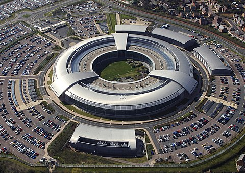 An aerial view of GCHQ's headquarters, 2004; the biggest employer in Gloucestershire is the intelligence agency GCHQ, who are based at 'The Doughnut', their headquarters[139] GCHQ has around 6,000 staff, MI5 has 4,000, and MI6 (Secret Intelligence Service) has 3,200; GCHQ is in the west of Cheltenham, off the A40 at the A4013 roundabout at Fiddlers Green, and also has a site to the east at Oakley