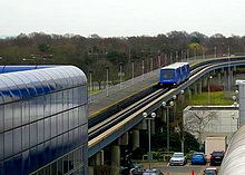Blue, three-car train approaching a station