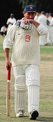 A cricket player facing the camera, walking off the pitch with his bat in his right hand, gloves in his left, wiping his mouth with his left hand