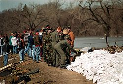 A line of people facing each other in an alternating manner are located next to a river. At the end of the line is a man putting a sandbag on top of a dike of numerous other sandbags. Multiple trees can be seen in the background.