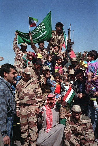 Civilians and coalition military forces wave Kuwaiti and Saudi Arabian flags as they celebrate the reversal of the annexation of Kuwait by Iraq (28 February 1991). Gulf War Saudi Flag.JPEG