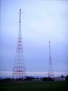 Two metal-truss radio towers against a blue sky.