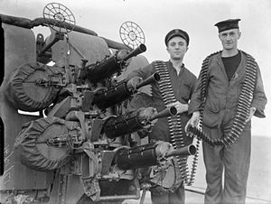 HMS London (69) - The gun crew of a .5-inch four barrelled Vickers gun at their quarter on board HMS London. Note the long belts of ammunition hanging off the two men.
