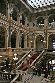 Vue intérieure d'un édifice imposant: il s'agit d'un grand escalier, au centre d'un grand hall. Les deux étages visibles sont constitués de couloirs à colonnade ouverts sur le hall.